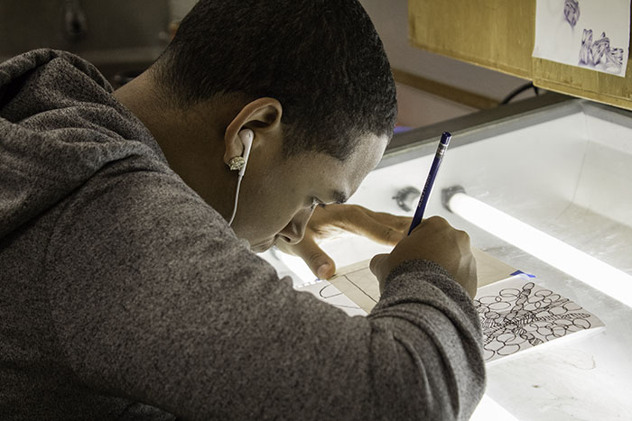 A drawing student uses a light box to trace his piece.
