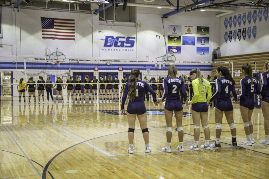 Both teams line up to listen to the national anthem before they begin the game.