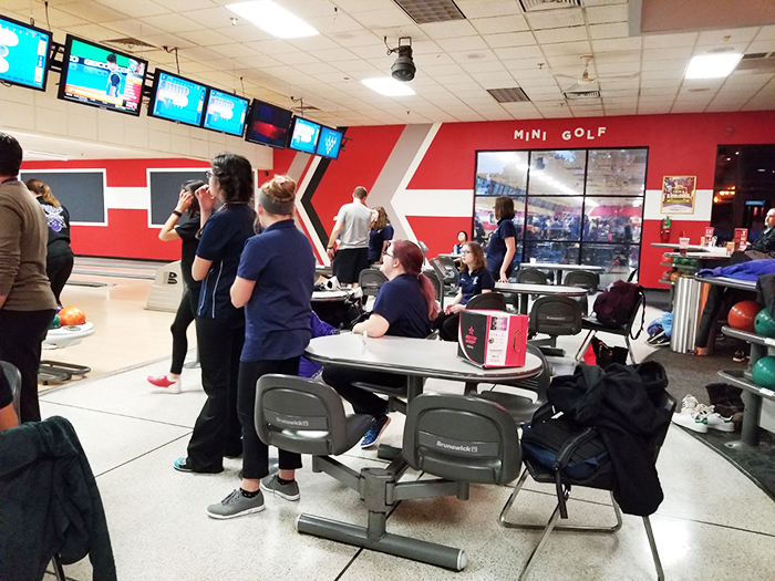 The DGS Girls' Bowling team waits for final scores at their match against DGN, held at the Brunswick Bowling Alley.