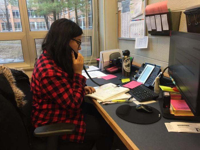 Attendance secretary Naybeth Moreno operating the phone in the attendance office.