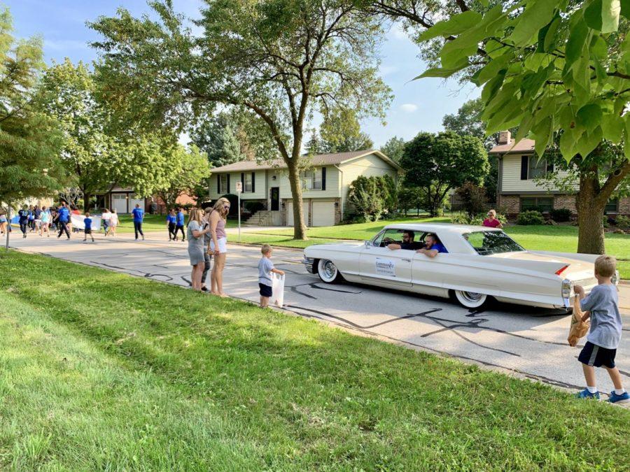 Social studies teacher Jordan DeLay drives a classic car as he hands out candy to neighborhood children.
