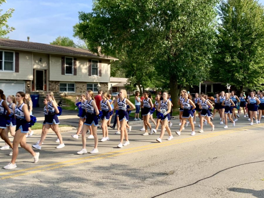 The dance team performs their routine while marching in the parade.