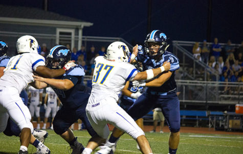 DGS offensive lineman blocking Wheaton North player at a home game.