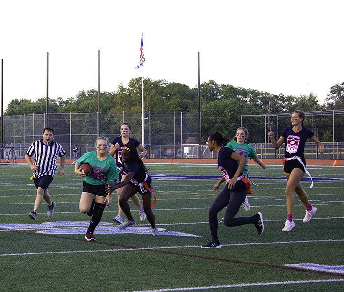 Freshman Anna Marten runs with the ball while junior Aamari Taylor tries to rip her flag off.