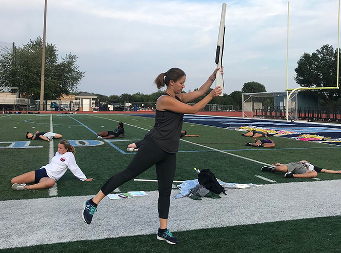 New teacher and color guard coach Stephanie Peterson rehearsing at color guard practice.