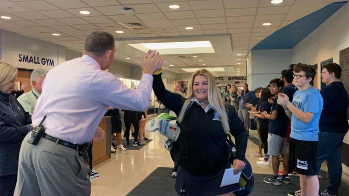 Brindza high fives Principal Edward Schwartz at her state send off at 7:30 a.m. on Oct. 17.