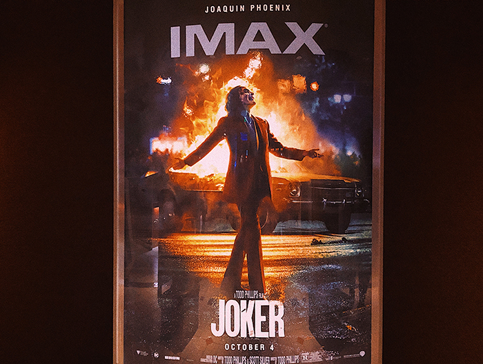 The Joker stands nonchalantly amongst chaos in the film's promotional poster.