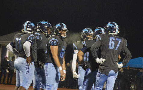 A group of offensive linemen gathering together during a timeout. The temperature was cold enough to see the breath coming from their mouth and the steam coming off of the players' jerseys while they were sweating.