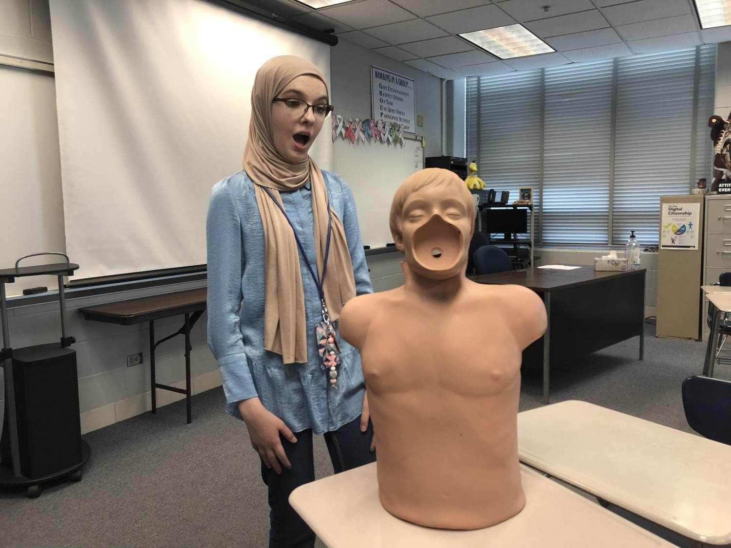 Ensara shows her discomfort with the CPR dummies popular in DGS health classes.