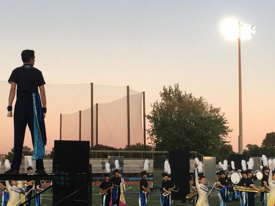 The DGS Marching Mustangs, led by Nick Sisson alongside three other drum majors, performs in exhibition at the blue on blue scrimmage.