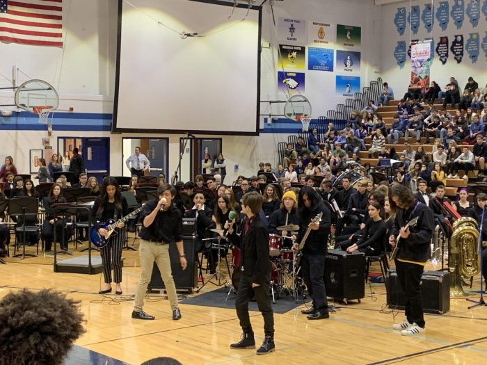 The rock band class performs their piece at the holiday concert assembly for the students. The rock band being included in the show is new this year.