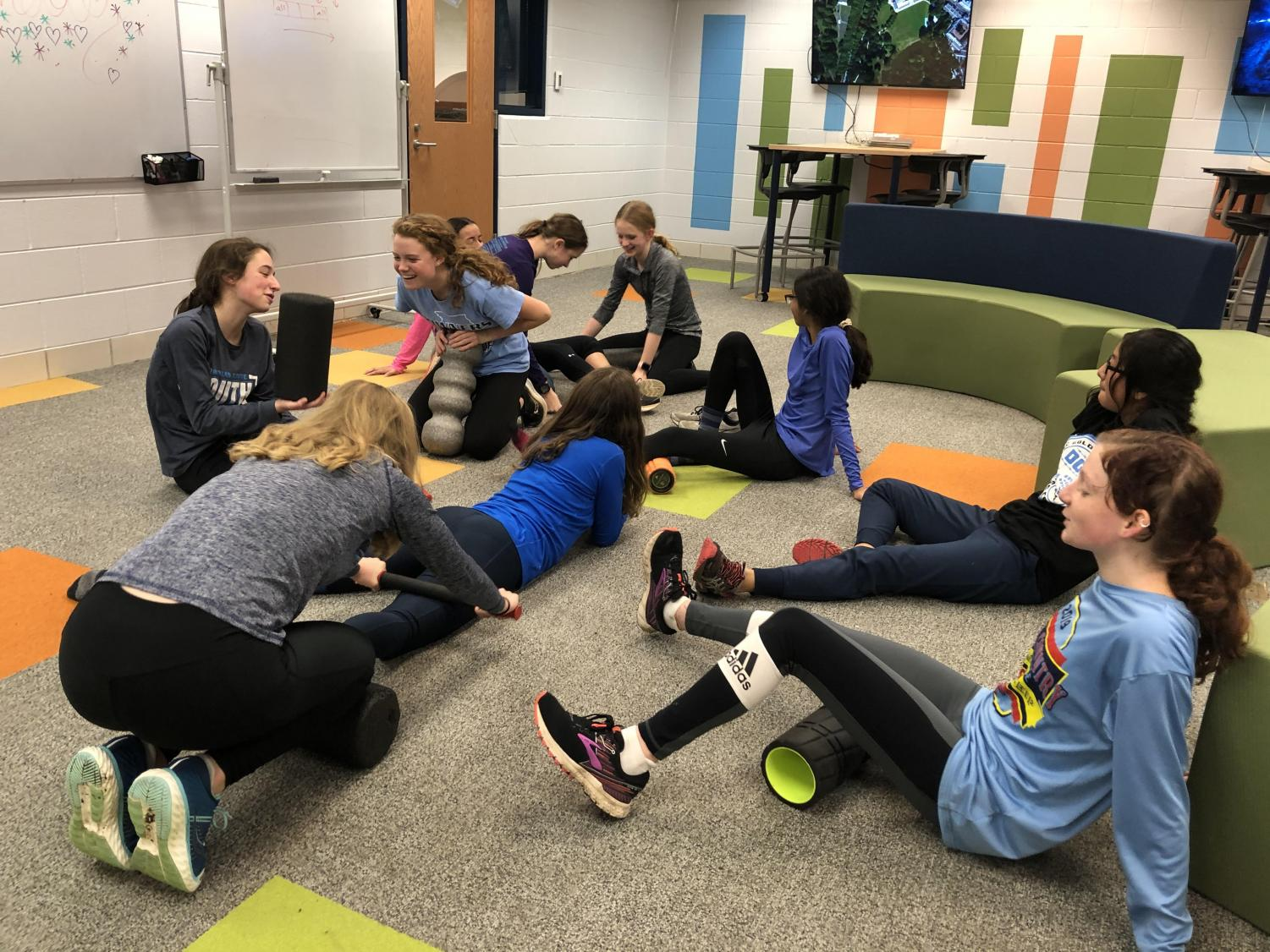 Distance members of the girls track and field team recover after a day of training.