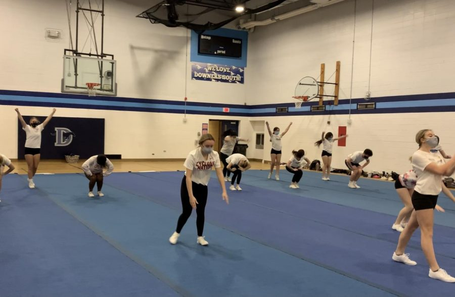 Cheerleaders perform a combination of tumbling, dance and jumps during their competitive routine.