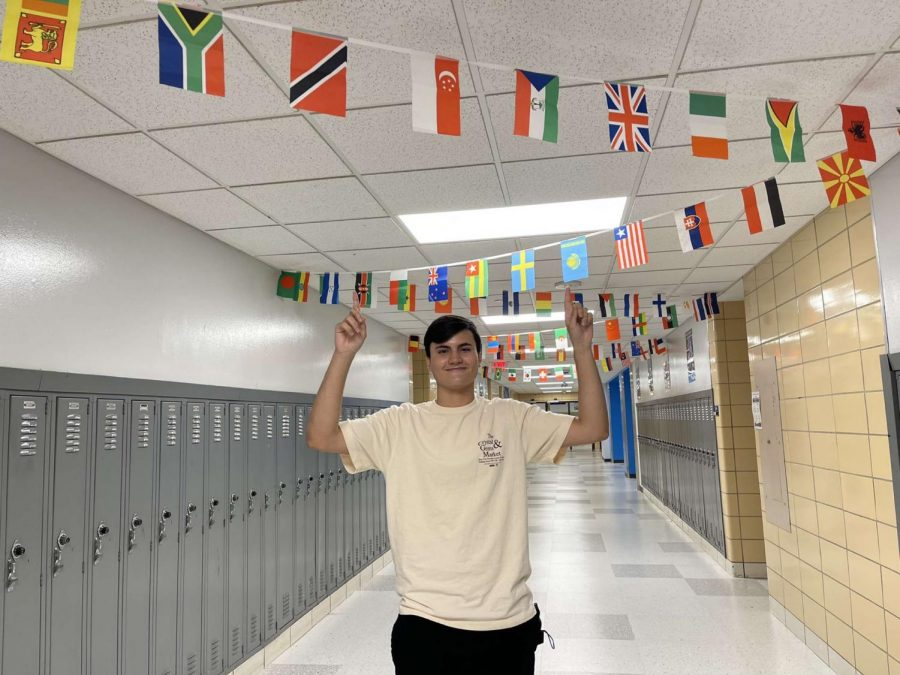 Papavero poses near his language classroom where he practices speaking French, his fourth language, almost everyday.